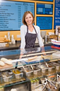 Woman standing at counter in restaurant smiling