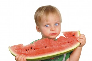Cute little baby boy is having a watermelon
