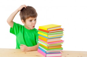 Boy with books scratching his head